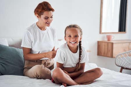 Mother combing her daughter hair 版權商用圖片