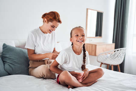 Mom making braids for her daughter