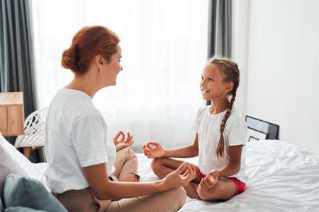 Mother and girl sitting in lotus pose