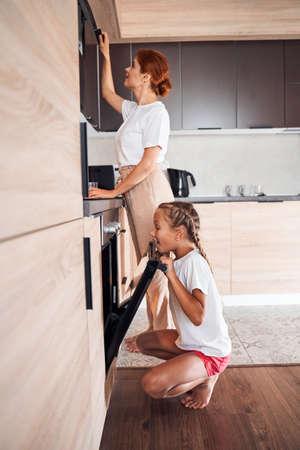 Girl looking inside an oven 版權商用圖片