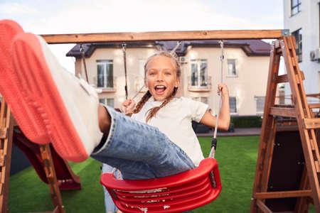 Girl swinging at playground Stok Fotoğraf