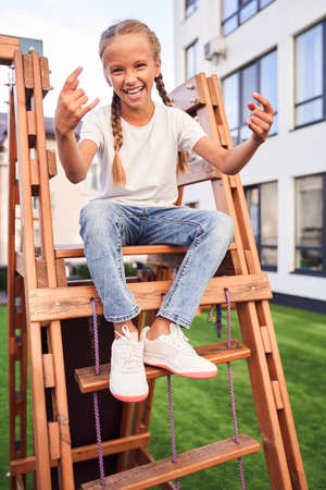 Girl sitting on the wooden slide
