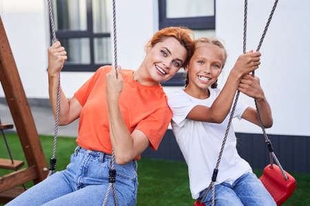 Mother sitting at the swings with her daughter