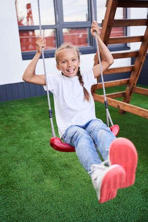 Schoolgirl playing on a swing Stok Fotoğraf