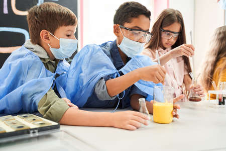 Two curious boys in protective masks and gowns mixing liquids