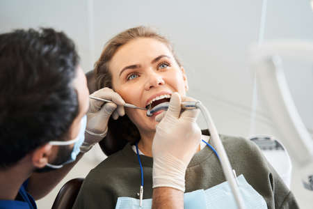 Smiling blond woman having her teeth examined by skilful dentist