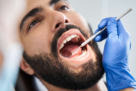 Bearded man in dentist chair ready for regular check up