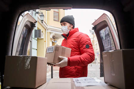 Serious courier stands near trunk of car with parcels