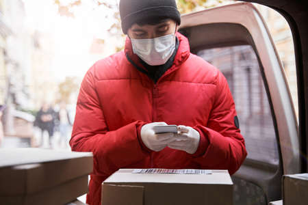 Courier in mask holding smartphone while scanning a barcode Stock Photo