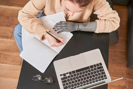 Girl with prosthesis arm writing something at the notebook Zdjęcie Seryjne