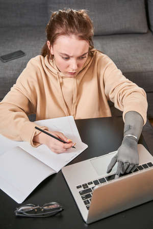 Woman with prosthesis arm writing at notebook
