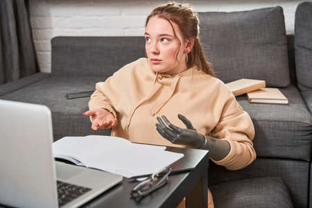 Ginger lady with prosthesis arm studying at home