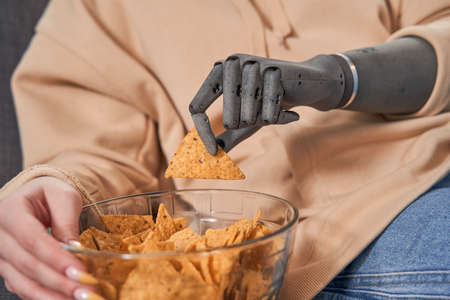 Woman with artificial limb sitting at sofa and eating chips Zdjęcie Seryjne