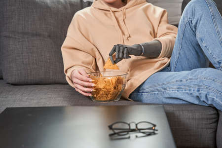 Woman with artificial limb eating chips while watching movie