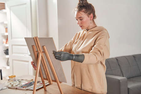 Female artist with artificial limb preparing to paints picture