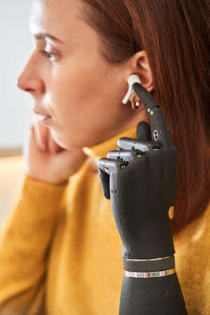 Lady with prosthesis arm inserting wireless earphones Stock Photo
