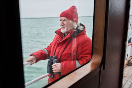 Captain of fishing boat holding his binoculars while looking away