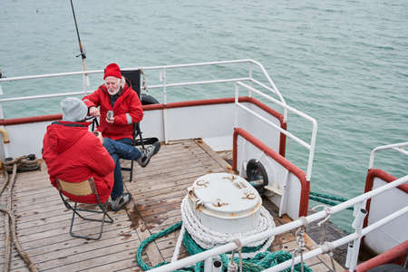 Fisherman sitting with his colleague at the boat during the work
