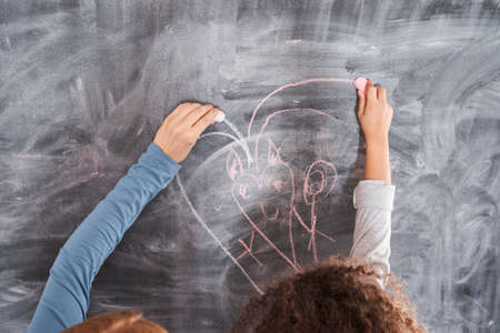 Mother and daughter drawing with chalks at the blackboard