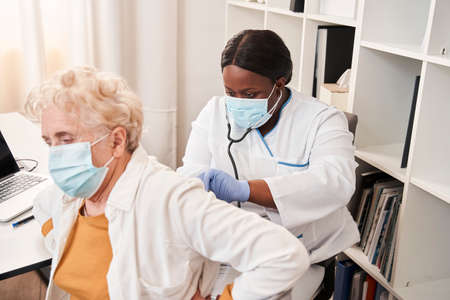 Woman doing regular checkup while examine mature client