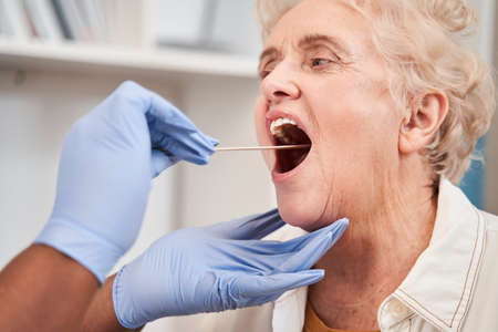 Doctor looking at the throat of senior patient at regular check