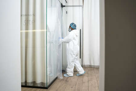 Doctor wearing protective equipment comes in to the isolation unit