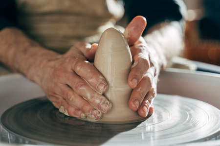 Potter makes pot of clay on potters wheel
