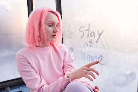 Girl with pink hair sitting at the windowsill and writing at the misted window