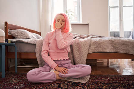 Woman with crossed legs and closed eyes meditating at home 版權商用圖片