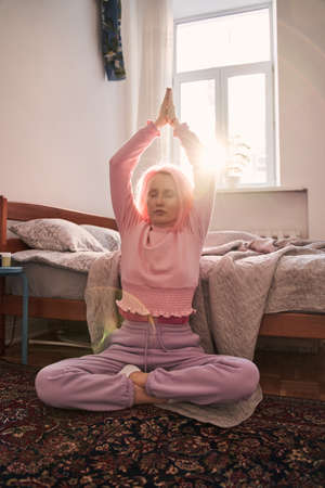 Girl sitting cross-legged and enjoying meditation in her bedroom 版權商用圖片