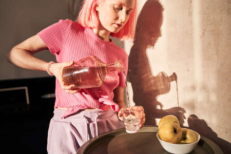 Woman with pink hair pouring water into the glass at the morning