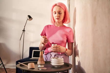Woman with pink hair stirring in a bowl for the matcha tea