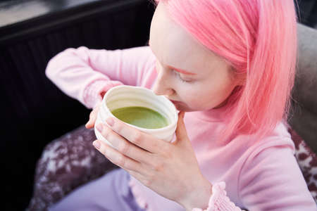 Girl who drinks healthy and delicious green matcha latte tea