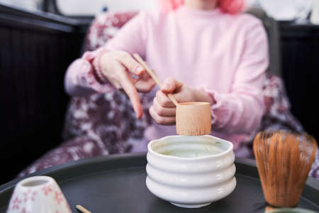Woman wearing pink clothes sitting at the table and preparing matcha tea