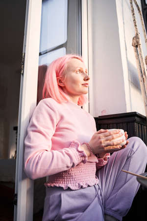 Girl with pink hair drinking healthy and delicious green matcha 版權商用圖片