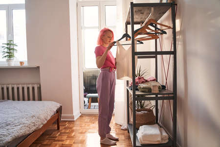 Woman goes through hangers with clothes while choosing look for the day 版權商用圖片
