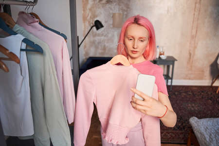 Woman with pink hair shooting with hanger with clothes at her smartphone