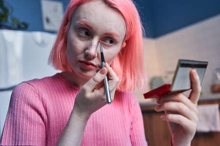 Woman with pink hair making vivid makeup at home at the kitchen