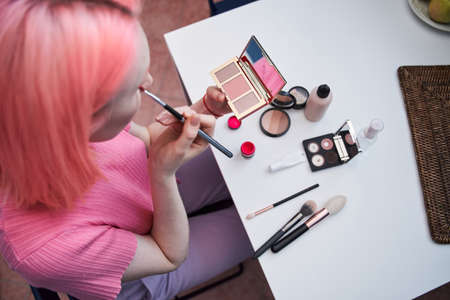 Woman with pink hair holding hand palette with shadows and mirror