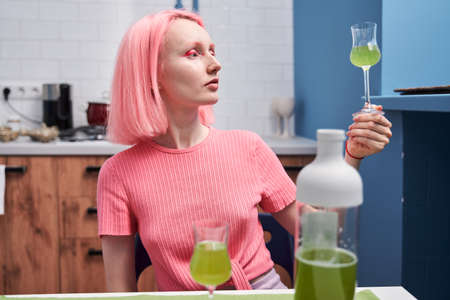Girl sitting at the kitchen and looking at the color of a matcha drink