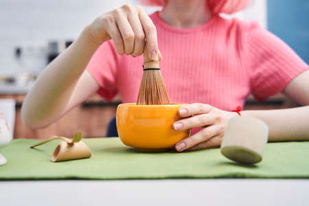 Woman holding modern whisk for whipping the matcha powder at home