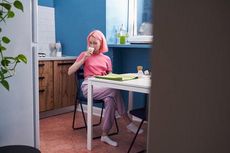 Woman drinking hot green tea matcha latte at home at the kitchen
