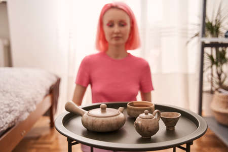 Woman with pink hair sitting at the room and preparing for the tea ceremony 版權商用圖片