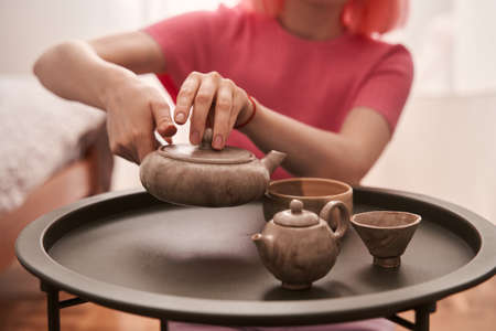 Woman with pink hair sitting at the room and pouring tea at the cups