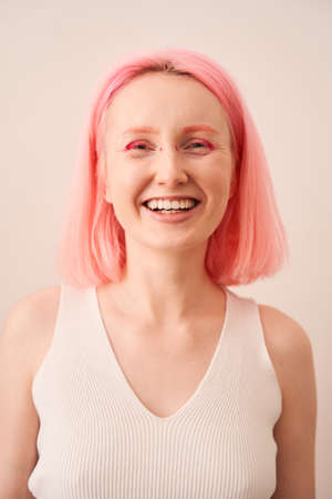 Woman with pink hair and vivid make up laughing