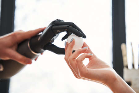 Engineer passes a tennis ball with the bionic prosthesis hand to his colleague