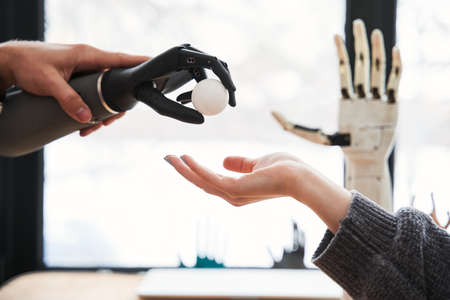 Engineer passes a tennis ball with the bionic hand to his female colleague