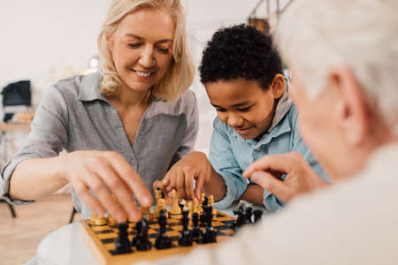 Boy sitting near of his parents and playing at chess with them