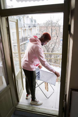 Man hanging clothes carefully on the dryer for clothes after washing