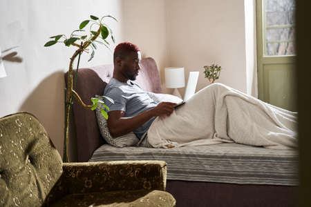 Man sitting at the bed after waking up and looking at his laptop with friendly smile